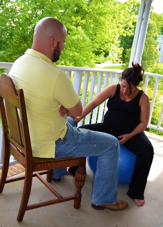 Partner providing pain relief for laboring mother with guidance from their doula.